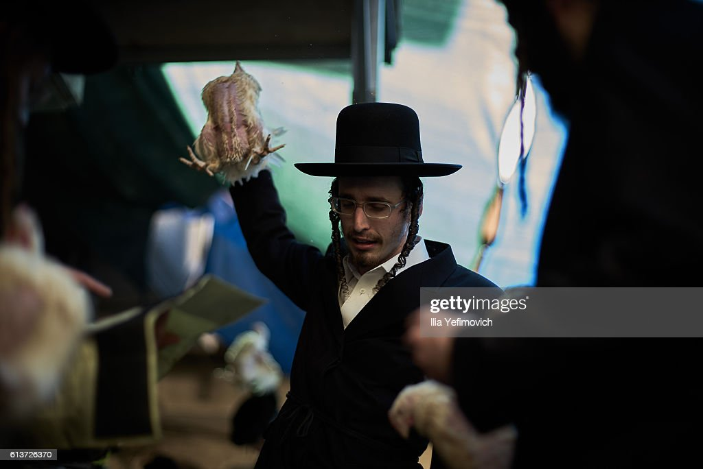 An Ultra-Orthodox Jewish man performs the Kaparot ceremony on October 10, 2016 in Jerusalem, Israel. It is believed that the Jewish ritual, which involves swinging a live chicken above one's head, transfers the sins of the past year to the chicken, which is then slaughtered and traditionally given to the poor. It is performed before the Day of Atonement, or Yom Kippur, the most important day in the Jewish calendar, which this year will start on sunset on October 11.