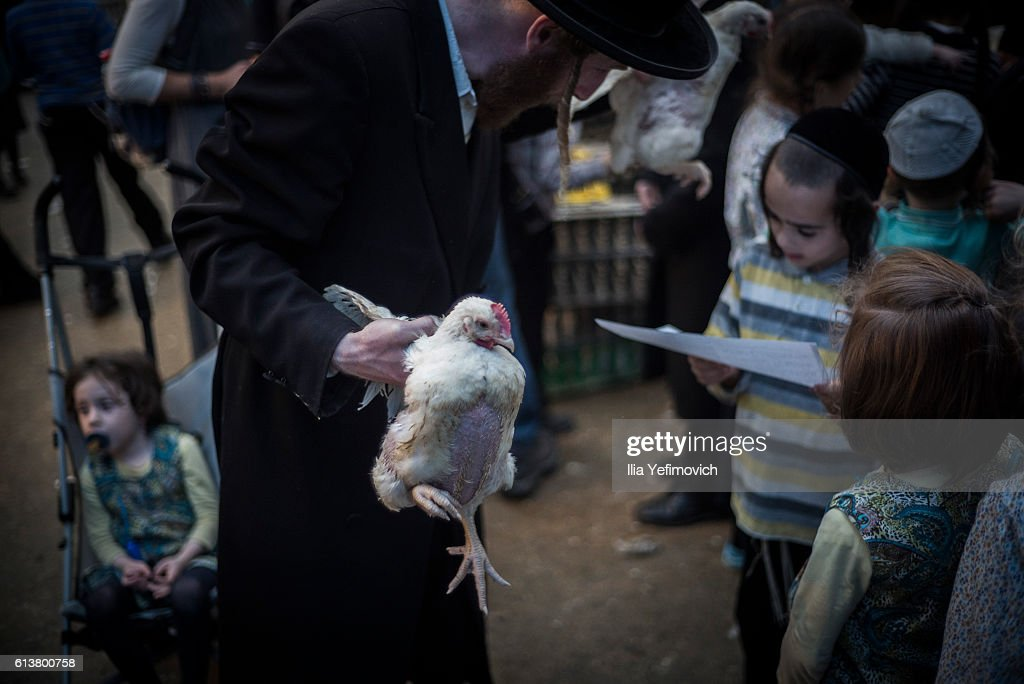 An Ultra-Orthodox Jewish man performs the Kaparot ceremony on October 10, 2016 in Jerusalem, Israel. It is believed that the Jewish ritual, which involves swinging a live chicken above one's head, transfers the sins of the past year to the chicken, which is then slaughtered and traditionally given to the poor. It is performed before the Day of Atonement, or Yom Kippur, the most important day in the Jewish calendar, which this year will start at sunset on October 11.