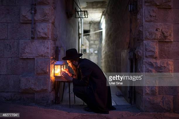 An UltraOrthodox Jewish man prays and lights candles on the fifth night of the Jewish holiday of Hanukkah the festival of light at the ultraOrthodox...