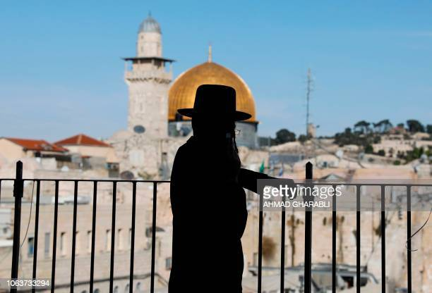 An UltraOrthodox Jewish man stands at the Jewish quarter in Jerusalem's Old City overlooking the Dome of the Rock of the alAqsa mosque on November 20...