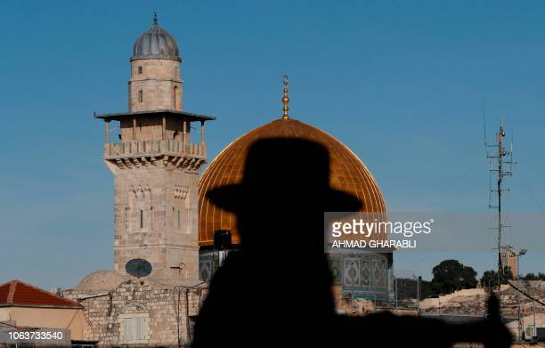 An UltraOrthodox Jewish man stands at the Jewish quarter in Jerusalem's Old City overlooking the Dome of the Rock in the alAqsa mosque on November 20...