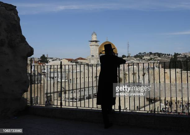 TOPSHOT An UltraOrthodox Jewish man stands at the Jewish quarter in Jerusalem's Old City overlooking the Dome of the Rock of the alAqsa mosque on...