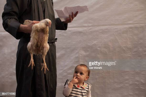 An UltraOrthodox Jewish man swings a chicken over his daughter's head as they perform the Kapparot ceremony on September 27 2017 in Jerusalem Israel...