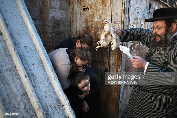 An ultraOrthodox Jewish man swings a chicken over his family as they perform the Kapparot ceremony in the ultraOrthodox neighbourhood of Mea Shearim...