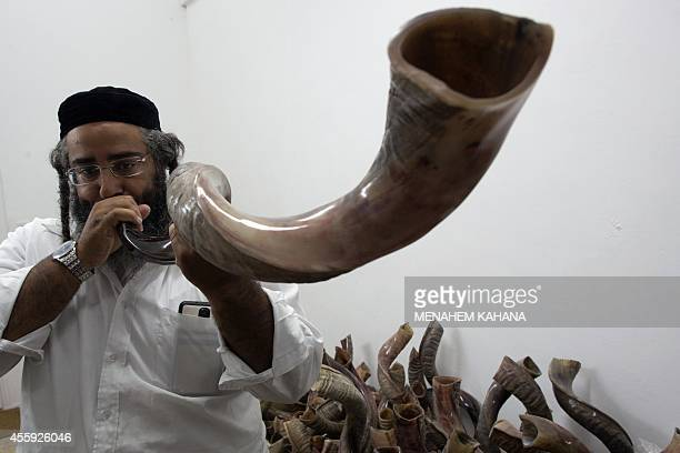 An UltraOrthodox Jewish man tests a Shofar before buying it at a factory in Tel Aviv on September 22 2014 ahead of the Jewish New Year The Shofar...