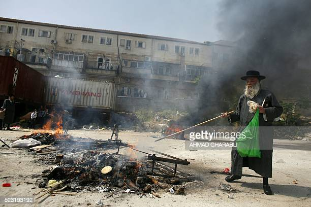 An UltraOrthodox Jewish man throws bread into a fire as they burn leavened items on April 22 2016 in Jerusalem during the final preparations before...
