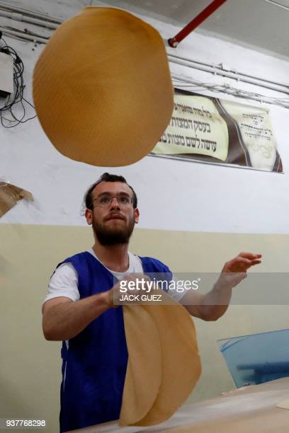 An UltraOrthodox Jewish man transfers the Matzoth to be baked on March 25 2018 at a bakery in Kfar Habad near Tel Aviv Religious Jews throughout the...