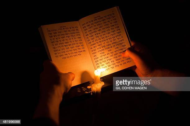 An ultraOrthodox Jewish man uses a candle to read from the book of Eicha during the annual Tisha B'Av fasting and a memorial day commemorating the...