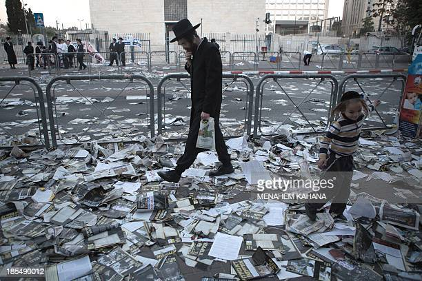 An Ultraorthodox Jewish man walks at a street covered with election campaign leaflets in Jerusalem on October 21 2013 on the eve of Israel's...