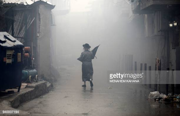 TOPSHOT An UltraOrthodox Jewish man walks down a street through the smoke from burning leavened items during the Srefat Chametz ritual on March 30...