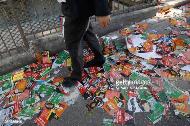 TOPSHOT An UltraOrthodox Jewish man walks in a street littered with election campaign posters for the upcoming Jerusalem municipal elections in...