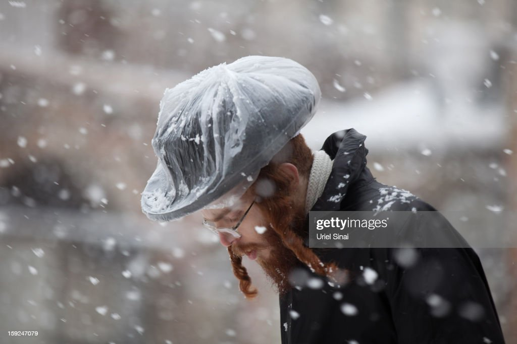 An Ultra-orthodox Jewish man walks in the snow in the Mea Shearim religious neighborhood on January 10, 2013 in Jerusalem, Israel.