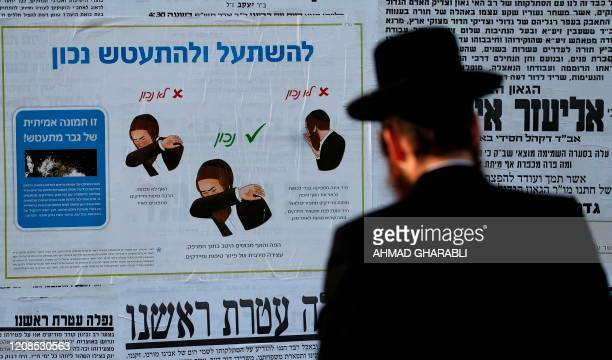 An UltraOrthodox Jewish man walks next to a billboard with instructions on how to properly sneeze in Jerusalem on March 29 amid measures to stem the...