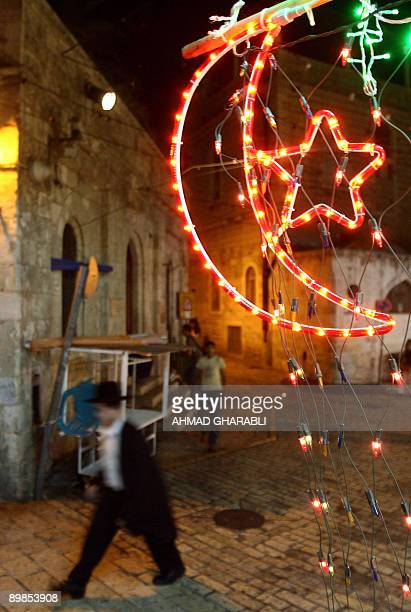 An ultra-Orthodox Jewish man walks past Ramadan decorations ahead of the Muslim holly fasting month in Jerusalem's old city on August 18, 2009....