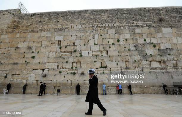 An ultra-Orthodox Jewish man wearing a plstic-covered hat and speaking on a phone walks past people praying at the nearly deserted Western Wall,...