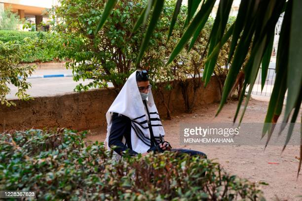 An UltraOrthodox Jewish man wearing a protective face mask due to the COVID19 coronavirus pandemic and Talit prayer shawl prays along a street...