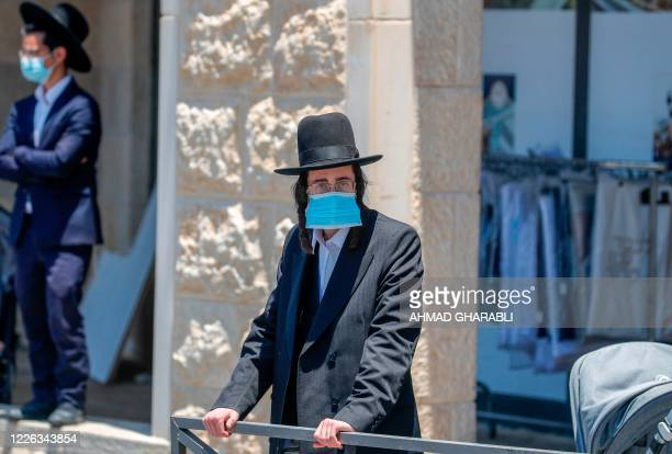 An UltraOrthodox Jewish man wearing a protective face mask stands at a checkpoint erected to block entrance to the neighbourhoods of Romema and...
