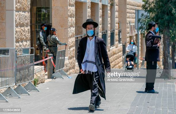 An Ultra-Orthodox Jewish man, wearing a protective face mask, walks past a checkpoint erected to block entrance to the neighbourhoods of Romema and...