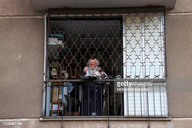 An UltraOrthodox Jewish man wearing a Talit prayer shawl prays in his home in the ultraOrthodox city of Bnei Brak near Tel Aviv on September 6 during...