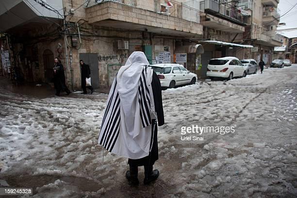 An Ultraorthodox Jewish man wears a praying shawl in the snow in the Mea Shearim religious neighborhood on January 10 2013 in Jerusalem IsraelÊ