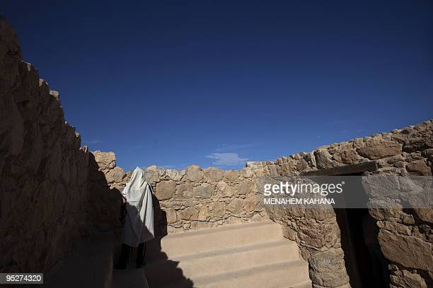 An ultraOrthodox Jewish man wrapped in a talit a prayer shawl prays in the ancient synagogue at the hilltop fortress of Masada in the Judean desert...