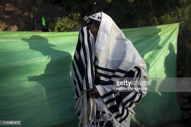 An ultraOrthodox Jewish man wrapped with the typical Talit praying shawl prays at the gravesite of Rabbi Shimon Bar Yochai in the northern Israeli...