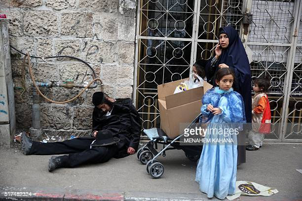 An ultraOrthodox Jewish mother and her children wearing costumes walk past a drunk man sitting on the pavement in Jerusalem Mea Shearim ultraOrthodox...