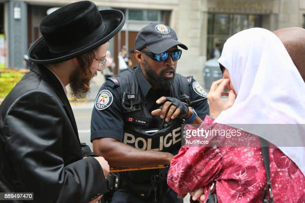 An UltraOrthodox Jewish Rabbi and a Palestinian woman speak with a member of the Toronto police during a demonstration in Toronto Canada on July 29...