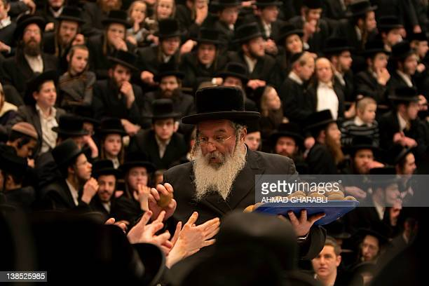An UltraOrthodox Jewish rabbi distributes fruits during a celebration by the Belz Hasidim of the Jewish feast of 'Tu Bishvat' or Tree New Year in...