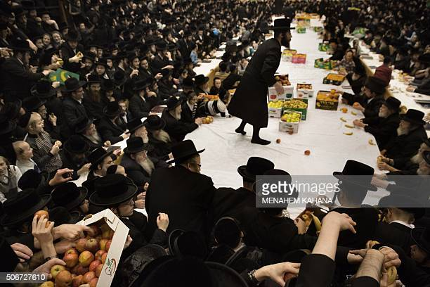 An UltraOrthodox Jewish rabbi of the Belz Hasidim distributes fruits during the celebration of the Jewish feast of Tu Bishvat on January 25 2016 in...