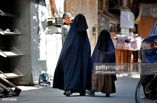 An ultraOrthodox Jewish woman and her daughter known in Israel as Neshot Ha Shalim or Frumka who cover themselves completely in a burqalike headtotoe...