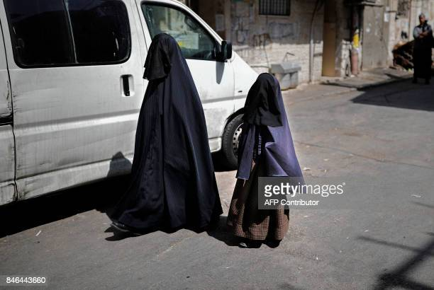 An ultraOrthodox Jewish woman and her daughter known in Israel as 'Neshot Ha Shalim' or 'Frumka' who cover themselves completely in a burqalike...