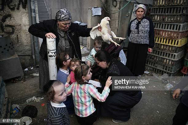 An ultraOrthodox Jewish woman swings a chicken over her family as they perform the Kapparot ceremony in the ultraOrthodox neighbourhood of Mea...