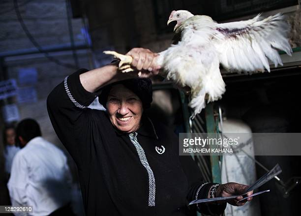 An UltraOrthodox Jewish woman swings a chicken over her head during the Kaparot ceremony in Mea Shearim neighborhood of Jerusalem on October 6 2011...