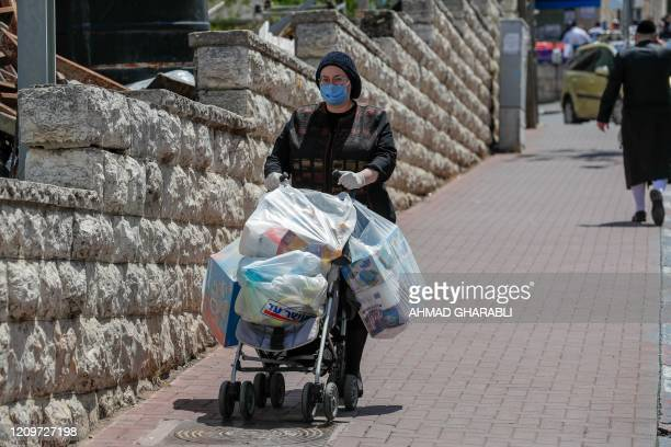 An ultraOrthodox Jewish woman wearing a protective face mask returns from shopping in Jerusalem's neighbourhood of Mea Shearim on April 12 during the...
