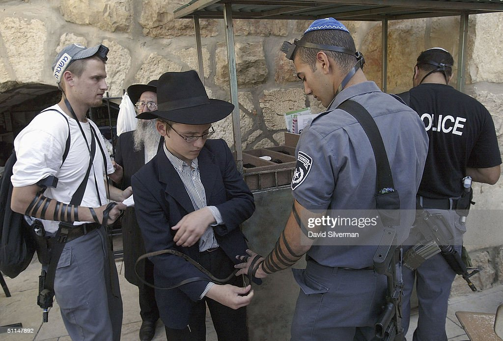 An ultra-Orthodox Jewish youth and his father help Israeli policemen wear Tefillin (phylacteries) during their morning prayers at the Western Wall, Judaism's holiest site, August 6, 2004, in Jerusalem's Old City. Some religious Jewish sects believe that by helping others to fulfill the Jewish commandments, they are strengthening their own faith and are bringing the Messianic era closer.