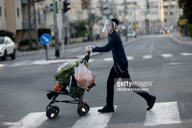 An Ultra-Orthodox Jewish youth wearing a protective plastic mask crosses a street with his shopping in the the Ultra-Orthodox Israeli city of Bnei...