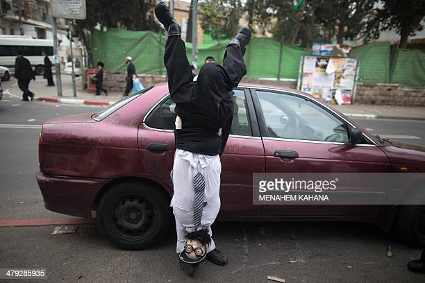 An UltraOrthodox Jewish youth wears a costume as he celebrates the Purim holiday in the ultraorthodox Mea Shearim neighborhood in Jerusalem on March...