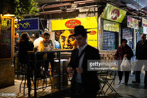 An ultraOrthodox man passes in front of a graffiti depicting an unrecognized woman which was painted over a closed shutter at the Mahane Yehuda...