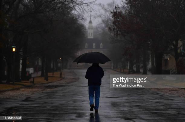 An umbrella clad pedestrian walks down a street during a light rain in Colonial Williamsburg on Tuesday February 12 2019 in Williamsburg VA