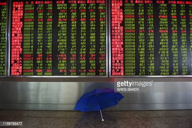 An umbrella dries in front of a screen showing stock prices at a securities company in Beijing on August 5 2019 Asian markets plummeted on August 5...