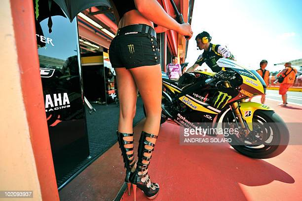 An umbrella girl stands in front of the Yamaha Teach 3 team during the MotoGP qualification section of the Italian Grand Prix at Mugello track on...