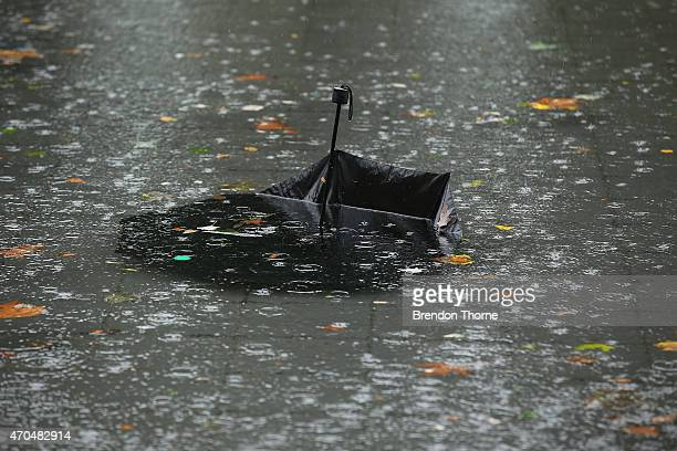 An umbrella is seen submerged in the ANZAC War Memorial pond in Hyde Park on April 21 2015 in Sydney Australia A second day of damaging winds and...