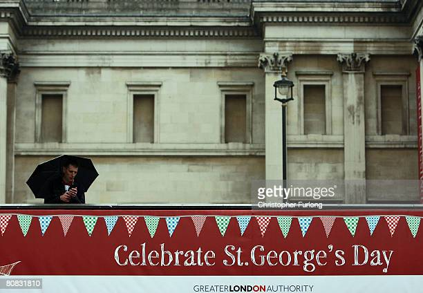 An umbrella protects a solitary man watching a theatre company during the festivities celebrating Saint Georges's Day in Trafalgar Square April 23...