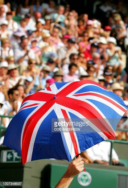 An umbrella with the Union Jack is help up as Andrew Murray of Great Britain plays Radek Stepanek of the Czech Republic during their second round...
