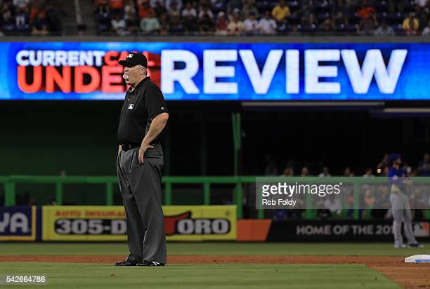 An umpire blows a bubble while a call is reviewed during the sixth inning of the game between the Miami Marlins and the Chicago Cubs at Marlins Park...