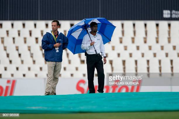 An umpire looks at the pitch as the macth is stopped due to rain during the third day of the second Test cricket match between South Africa and India...