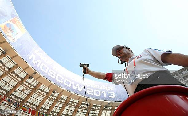 An umpire prepares to fire the starting pistol during the 100 metre qualifying event at the 2013 IAAF World Championships at the Luzhniki stadium in...