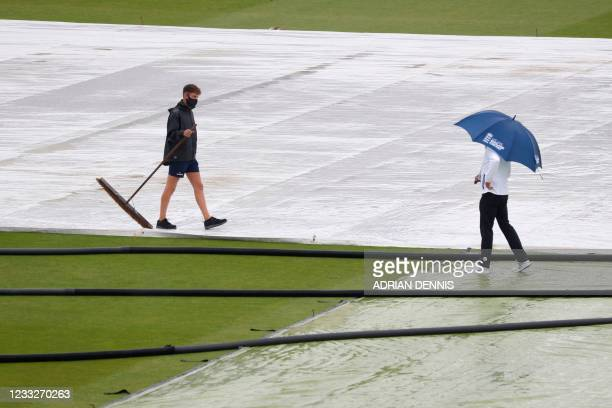 An umpire shelters under an umbrella during a pitch inspection as a groundstaff carries a brush after rain disrupted play on the third day of the...