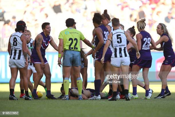 An umpire steps in to break up players during the round two AFLW match between the Fremantle Dockers and the Collingwood Magpies at Optus Stadium on...